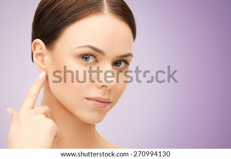 people, beauty, hearing and healthcare concept - face of beautiful woman touching her ear over violet background - stock photo