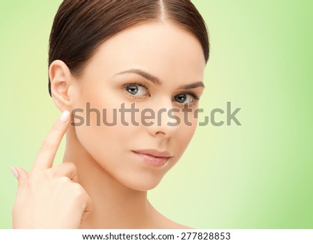 people, beauty, hearing and healthcare concept - face of beautiful woman touching her ear over green background