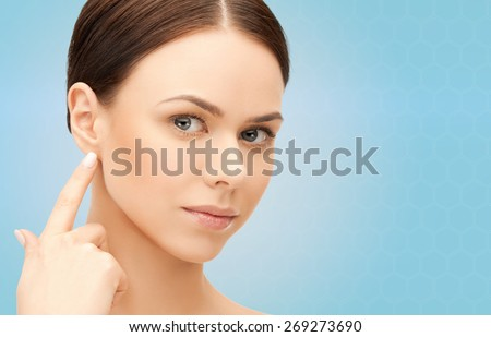 people, beauty, hearing and healthcare concept - face of beautiful woman touching her ear over blue background - stock photo