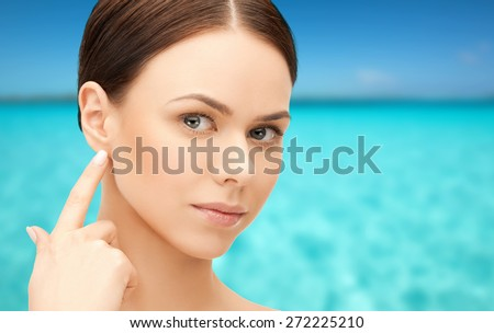 people, beauty, hearing and healthcare concept - face of beautiful woman touching her ear over blue sea and sky background - stock photo