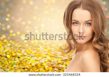 people, beauty, holidays , hair and skin care concept - beautiful woman with curly hairstyle over yellow autumn lights background - stock photo