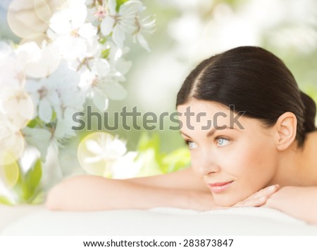 people, beauty, spa and body care concept - happy beautiful woman lying on massage desk over green natural cherry blossom background