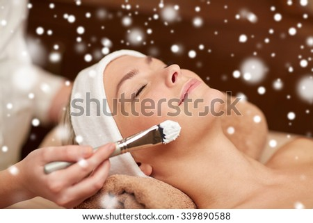 people, beauty, spa, cosmetology and skincare concept - close up of beautiful young woman lying with closed eyes and beautician hand applying facial mask by brush in spa salon with snow effect - stock photo