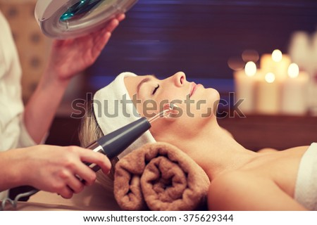 people, beauty, spa, cosmetology and technology concept - close up of beautiful young woman lying with closed eyes having face massage by massager in spa - stock photo