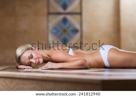 people, beauty, spa, healthy lifestyle and relaxation concept - beautiful young woman lying on hammam table in turkish bath - stock photo