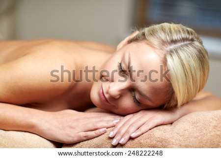 people, beauty, spa, healthy lifestyle and relaxation concept - close up of beautiful young woman lying on massage table in spa - stock photo
