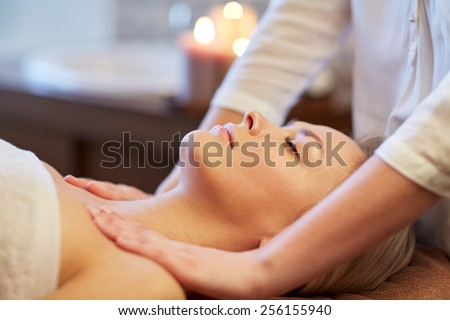 people, beauty, spa, healthy lifestyle and relaxation concept - close up of beautiful young woman lying with closed eyes and having massage in spa - stock photo