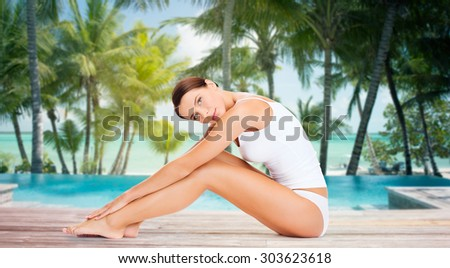 people, beauty, spa, travel and resort concept - beautiful woman in cotton underwear touching her legs over swimming pool on beach with palms background - stock photo