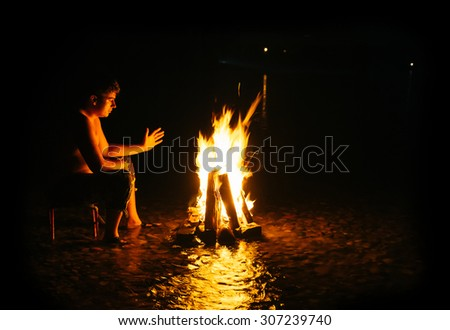 People - Bonfire on the river bank . Sparks, flames and other wonderful backgrounds for your text. photo framed wholly in black.