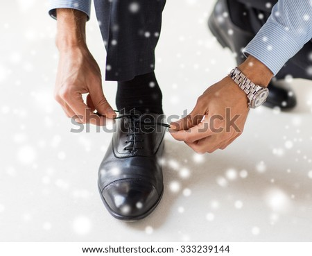 people, business, fashion and footwear concept - close up of man leg and hands tying shoe laces over snow effect over snow effect - stock photo
