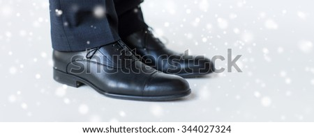 people, business, fashion and footwear concept - close up of man legs in elegant shoes with laces or lace boots over snow effect - stock photo