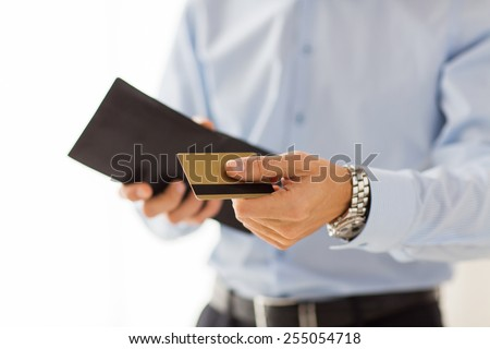 people, business, finances and money concept - close up of businessman hands holding open holding wallet and credit card - stock photo
