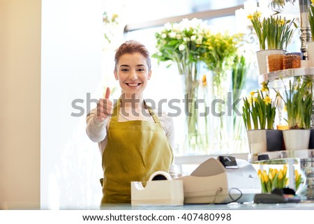people, business, sale and floristry concept - happy smiling florist woman at flower shop cashbox showing thumbs up