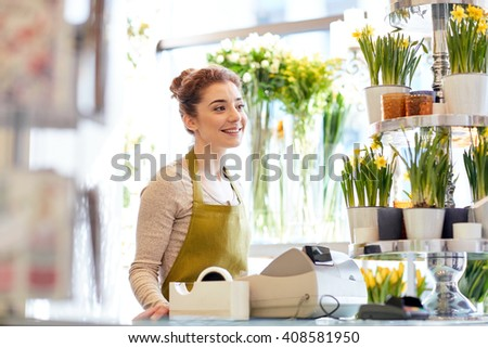 people, business, sale and floristry concept - happy smiling florist woman at flower shop cashbox - stock photo