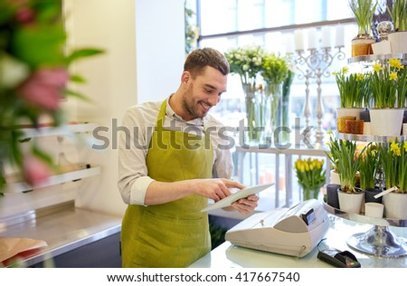 people, business, technology, sale and floristry and concept - happy smiling florist man with tablet pc computer at flower shop counter - stock photo
