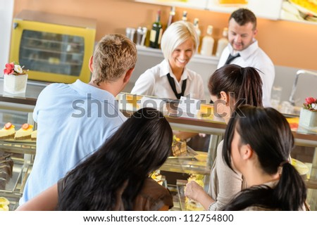 People buying cakes at cafe bar queue women  display dessert - stock photo