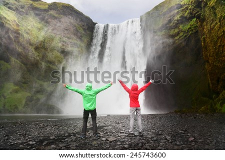 People by Skogafoss waterfall on Iceland golden circle. Couple visiting famous tourist attractions and landmarks in Icelandic nature landscape. - stock photo