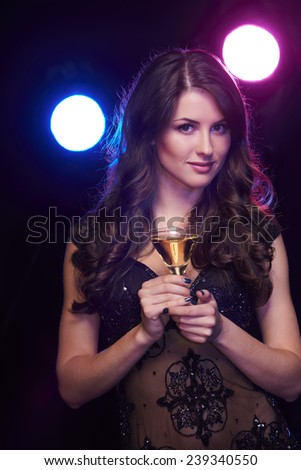 People celebration concept. Sensual woman with glass of cocktail over dark background - stock photo