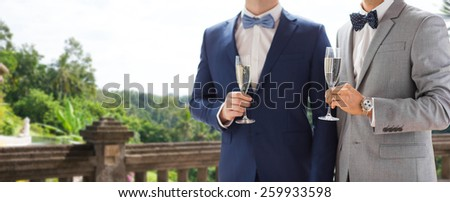 people, celebration, homosexuality, same-sex marriage and love concept - close up of happy married male gay couple drinking sparkling wine from glasses on wedding over balcony and nature background - stock photo