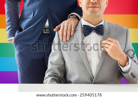 people, celebration, homosexuality, same-sex marriage and love concept - close up of male gay couple with wedding rings on putting hand on shoulder over rainbow flag background - stock photo