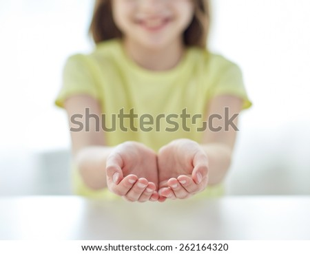 people, charity, childhood and advertisement concept - close up of child cupped hands at home - stock photo