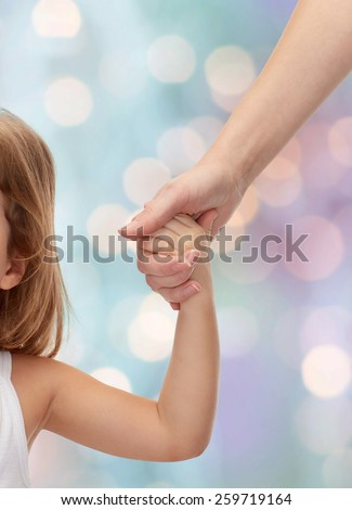 people, charity, family and adoption concept - close up of woman and little girl holding hands over holiday lights background - stock photo