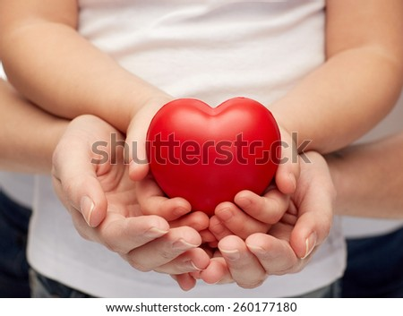 people, charity, family and advertisement concept - close up of woman and girl holding  red heart shape in cupped hands - stock photo