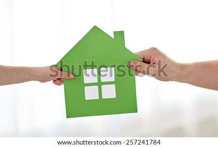 people, charity, family and home concept - close up of child and parent hands holding green paper house cutout - stock photo