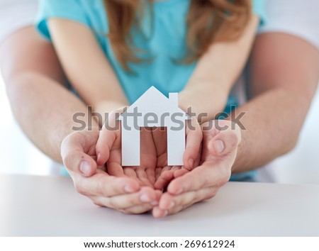people, charity, family, real estate and home concept - close up of man and girl holding green paper house cutout in cupped hands - stock photo