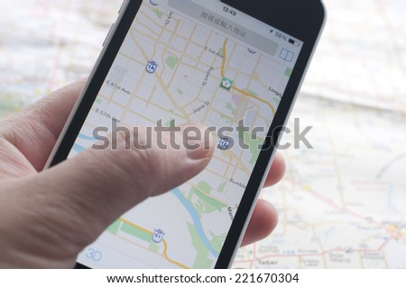 People checking smartphone with GPS navigator on map  - stock photo