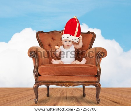 people, childhood and royalty concept - happy baby boy in royal hat with lollipop sitting on chair over blue sky and cloud background - stock photo