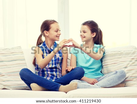 people, children, friends and friendship concept - happy little girls sitting on sofa and showing heart shape hand sign at home - stock photo