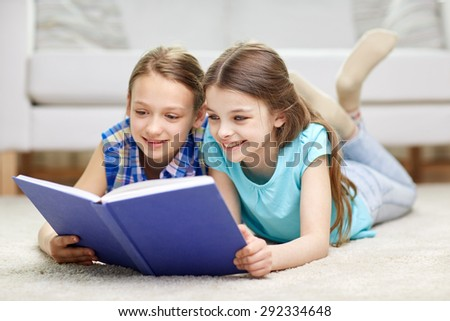 people, children, friends, literature and friendship concept - two happy girls lying on floor and reading book at home - stock photo