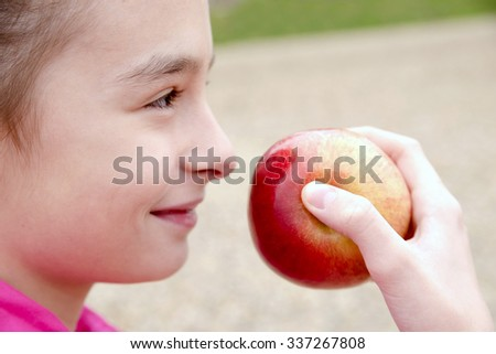 people, children, healthy eating and food concept- happy girl holding red apple - young cheerful attractive smiling girl eating red ripe apple - stock photo