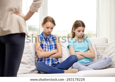 people, children, misbehavior, friends and friendship concept - upset feeling guilty or displeased little girls sitting on sofa and angry mother at home - stock photo