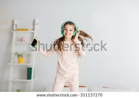 people, children, pajama party and technology concept - happy smiling girl in headphones jumping on bed with smartphone and listening to music at home - stock photo