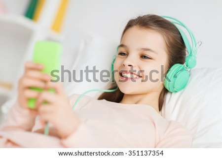 people, children, rest, and technology concept - happy smiling girl lying awake with smartphone and headphones in bed listening to music at home - stock photo