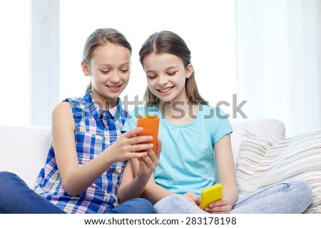 people, children, technology, friends and friendship concept - happy little girls with smartphones sitting on sofa at home - stock photo