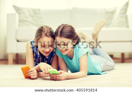 people, children, technology, friends and friendship concept - happy little girls with smartphones lying on floor at home - stock photo