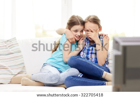 people, children, television, friends and friendship concept - two scared little girls watching horror on tv at home - stock photo