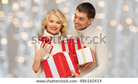 people, christmas, holidays and new year concept - happy family couple in sweaters holding gifts or presents over lights background