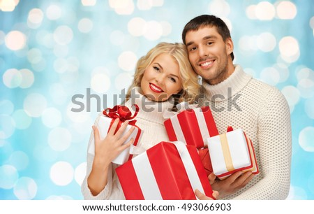 people, christmas, holidays and new year concept - happy family couple in sweaters holding gifts or presents over blue lights background