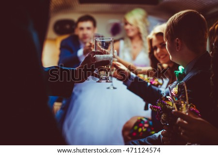 People clang glasses with champagne while sitting in the limousine
