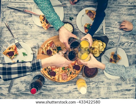 people clanging glasses together having pizza top view - stock photo