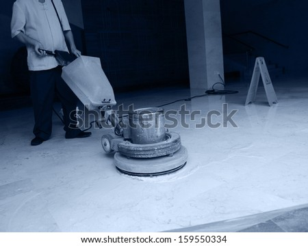 People cleaning floor with machine. - stock photo