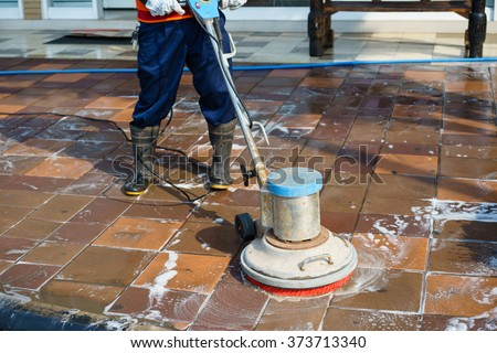 People cleaning floor with machine - stock photo