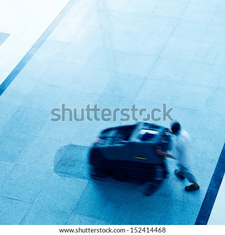 People cleaning floor with machine. blur motion - stock photo