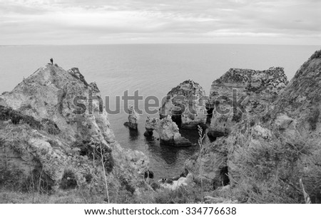 People climbing on the cliffs to see stone arches, caves and rock formations at Dona Ana Beach (Lagos, Algarve coast, Portugal) in the evening light. A view from above. Aged photo. Black and white. - stock photo