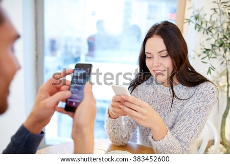 people, communication and dating concept - happy couple with smartphones at cafe or restaurant