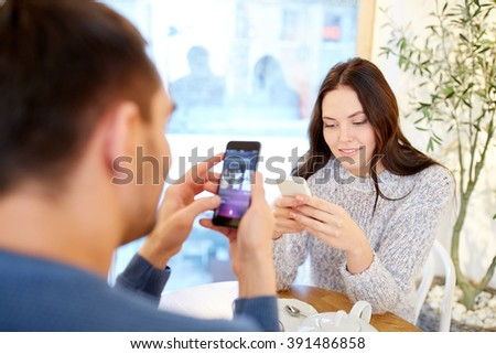 people, communication and dating concept - happy couple with smartphones drinking tea at cafe or restaurant - stock photo